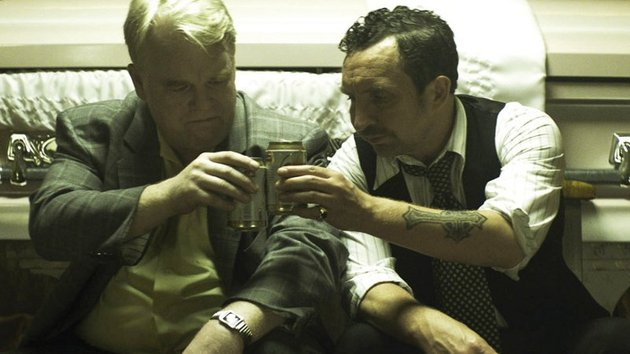 Sharing a drink by a coffin in God's Pocket. The late Philip Seymour Hoffman as Scarpato and Eddie Marsan as Smilin' Jack Moran, the fiery undertaker.