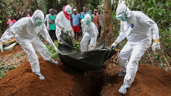 Liberian nurses bury the body of an Ebola victim on the outskirts of Monrovia in Liberia