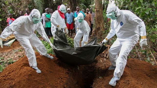 Liberian nurses bury the body of an Ebola victim on the outskirts of Monrovia in Liberia