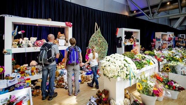 Visitors look at flowers and teddy bears in a memorial space at Schiphol Airport in Amsterdam