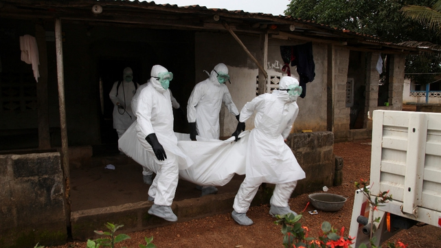 Liberian nurses carry the body of an Ebola victim from a house for burial in the Banjor Community on the outskirts of Monrovia