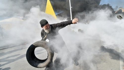 An Orthodox priest throws a tyre as Maidan self-defence activists clash with fighters of Kiev-1 volunteer battalion on Independence Square in Kiev