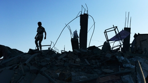 A Palestinian boy walks on the rubble of his destroyed home in  Gaza City