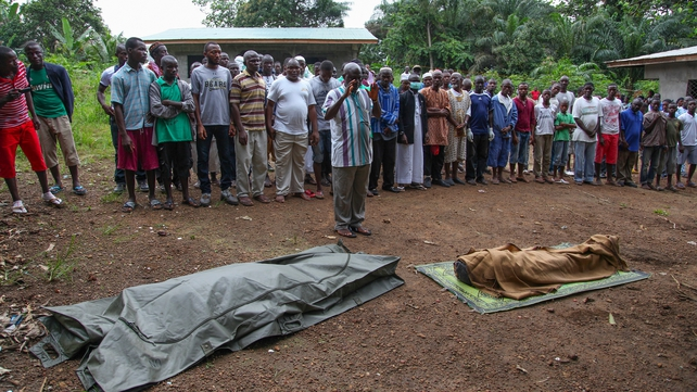 Liberian Muslims pray before burying the bodies of Ebola victims