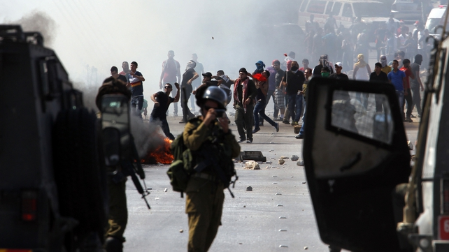 Palestinian protesters hurl stones at Israeli soldiers during clashes near the West Bank city of Nablus