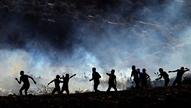 Palestinian protesters hurl stones during clashes near the West Bank city of Nablus