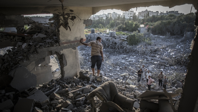 A Palestinian man stands in the remains of his living room after his home was hit by an Israeli airstrike in Gaza City