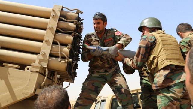Kurdish peshmerga fighters load missile launcher during clashes with Islamic State fighters