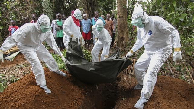 Liberian nurses bury the body of an Ebola victim
