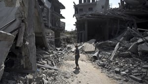 A Palestinian man stands amid the rubble of buildings following an Israeli military strike in Gaza.