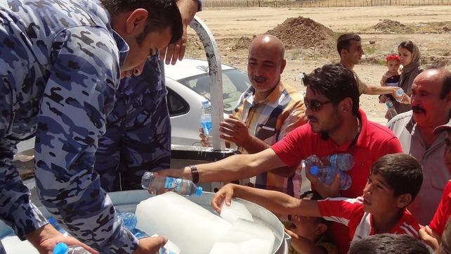 Iraqi military personnel distribute water to Shia Iraqi Kurds