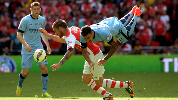 Arsenal's Mathieu Debuchy and Aleksandar Kolarov of City collide