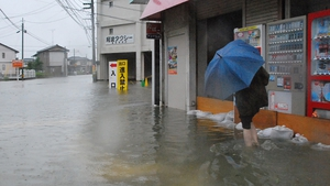 A local resident walks in a flooded street caused by Typhoon Halong's passing in Tokushima