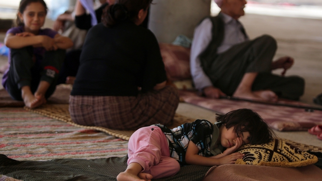 A child sleeps as Iraqi Yazidis take refuge inside a building under construction