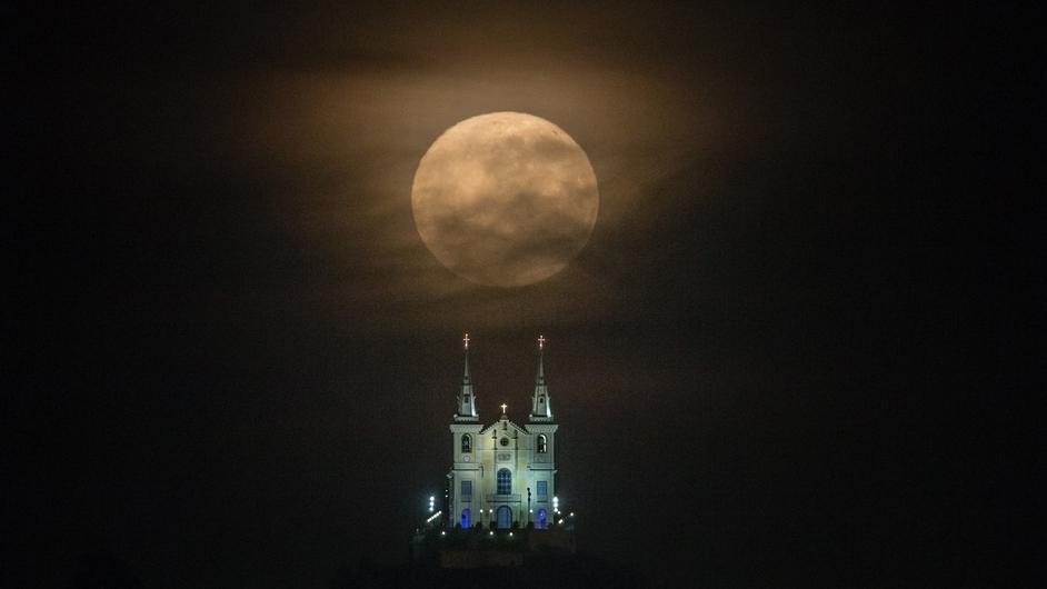 The supermoon descends behind the Nossa Senhora da Penha Church in Rio de Janeiro