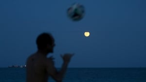 A man plays soccer in Miami Beach, Florida, on the night of the supermoon