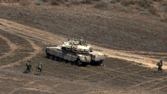 Israeli soldiers walk past a tank holding a position along the border with Gaza