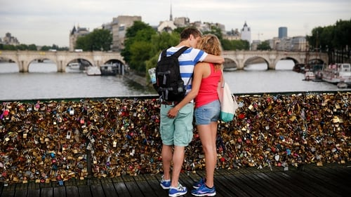 A couple kisses on the Pont des Arts