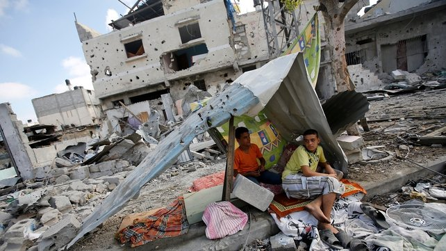 Two Palestinian brothers next to their destroyed house in Gaza's Al-Shejaeiya neighbourhood