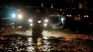 Commuters attempt to navigate the submerged streets of Manila in the Philippines