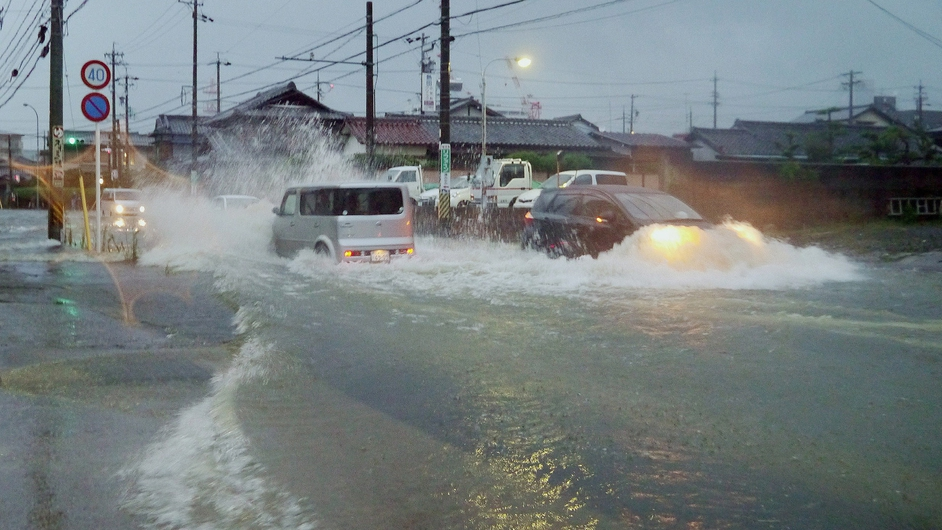 Vehicles drive down a flooded road in the city of Tsu as Typhoon Halong brought torrential rain to Japan
