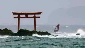 A windsurfer passes a torii gate shrine helped along by waves caused by the Typhoon in Hayama, Japan
