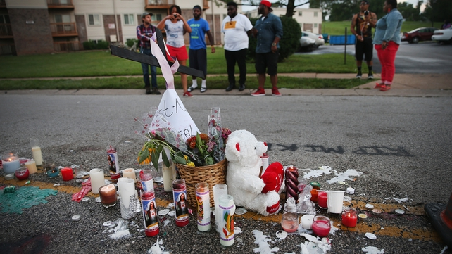 People view a memorial in the street where 18-year-old Michael Brown was shot by police