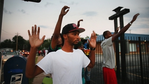 Protesters are forced by police from the business district into nearby neighbourhoods in Ferguson