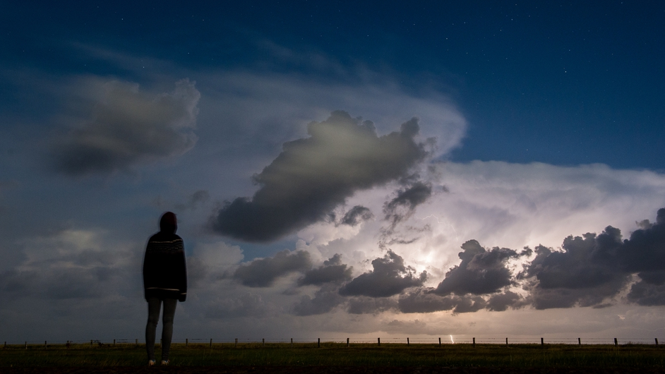 A woman looks out to sea in Westerhever, Germany, as a storm rages over the North Sea