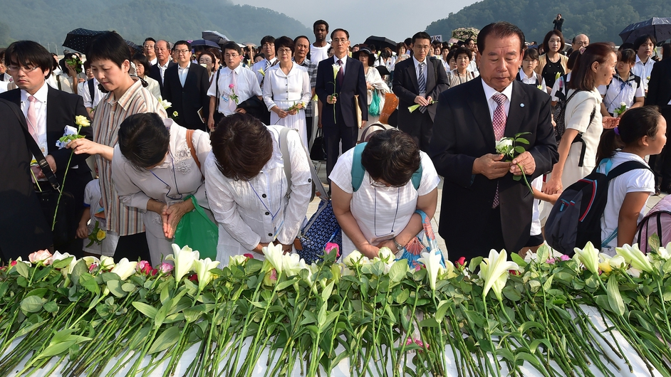 Followers of the Unification Church lay flowers in front of a portrait of the church's founder Reverend Sun Myung Moon before a ceremony to mark the second anniversary of his death