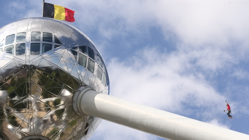 A slackliner walks between two spheres of the Atomium in Brussels, Belgium