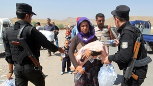 Peshmerga forces hand out water bottles to displaced Iraqi families from the Yazidi community