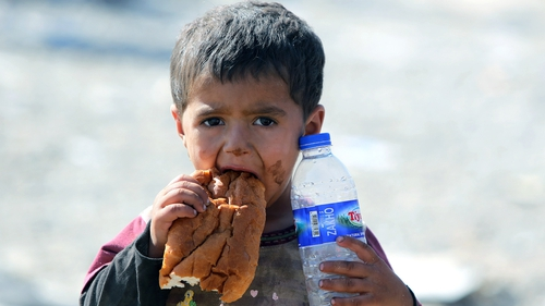 A boy is given bread and water as he waits at the Iraqi-Syrian border