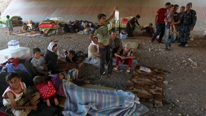 Iraqi Yazidis gather at a makeshift shelter in Dohuk