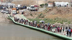 People cross the Fishkhabur Bridge over the Tigris River in northern Iraq