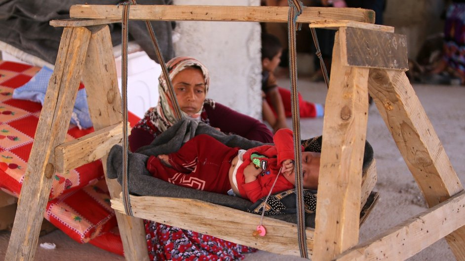 A woman sits next to a baby as they shelter inside a building under construction in the Kurdish city of Dohuk