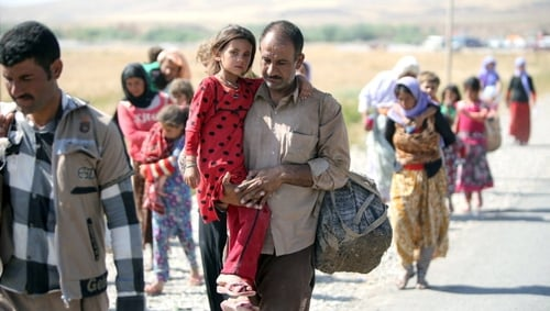 A displaced Iraqi man from the Yazidi community carries his daughter as they cross the Iraqi-Syrian border