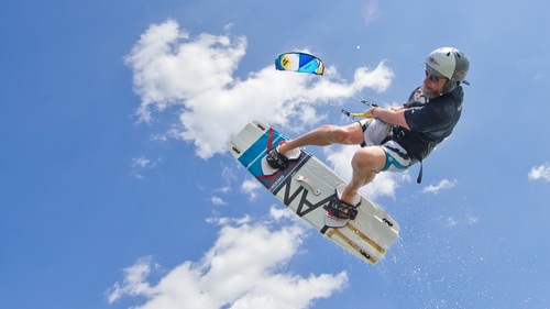 A kite surfer jumps into the air with his kiteboard at Lake Steinhude in Mardorf, Germany