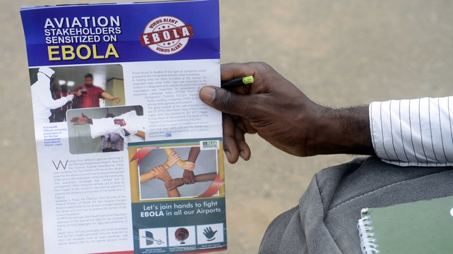 A man holds a flyer on the Ebola virus at the Murtala Muhammed International Airport in Lagos