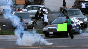 People scatter as St Louis County Tactical Police officers fire tear gas along West Florissant Road