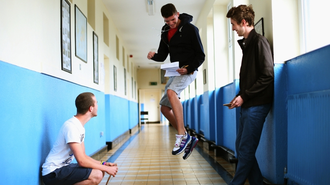Lee Shields (C) celebrates as Ciaran Keenan (L) and Ross Gaughran, prepare to open their results at St Vincent's CBS