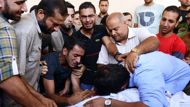 Family and friends mourn over the body of Palestinian translator Ali Abu Afash