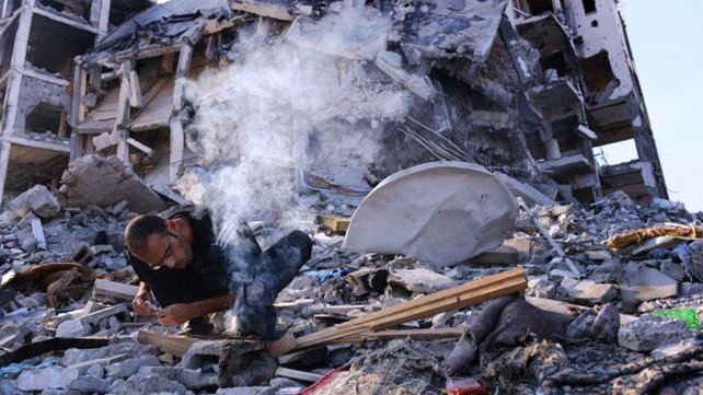 A man starts a small fire to heat water for tea after his home was damaged in fighting between Israel and Hamas