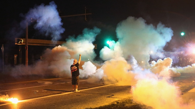 A demonstrator stands his ground as police fire tear gas