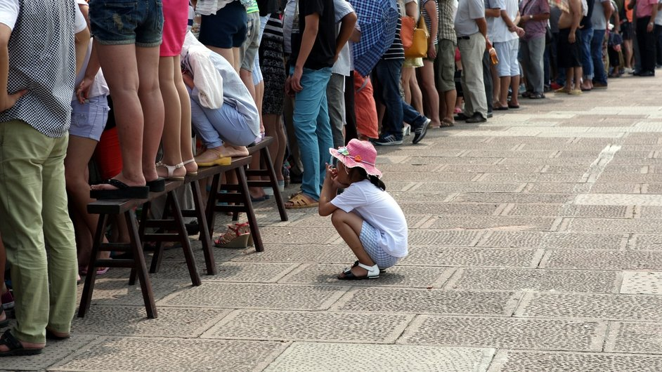 A little girl squats behind a row of adults watching the high tides of China's Qiantang River on a day of high tides