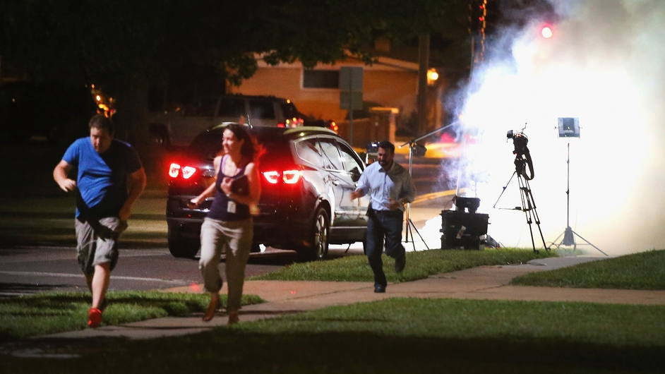 An Al Jazeera television crew, covering the protests about the shooting of Michael Brown in Missouri, scramble for cover as police fire tear gas at their position