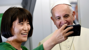 Pope Francis posing for a photo with a South Korean journalist aboard his flight on the way to Seoul