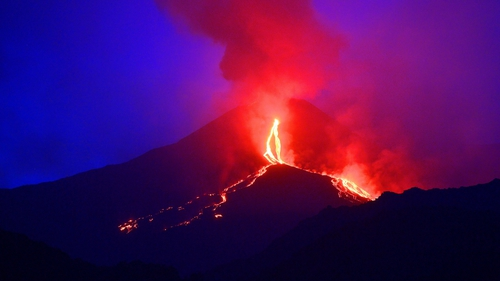 Lava flows from the Mount Etna volcano on the Italian island of Sicily