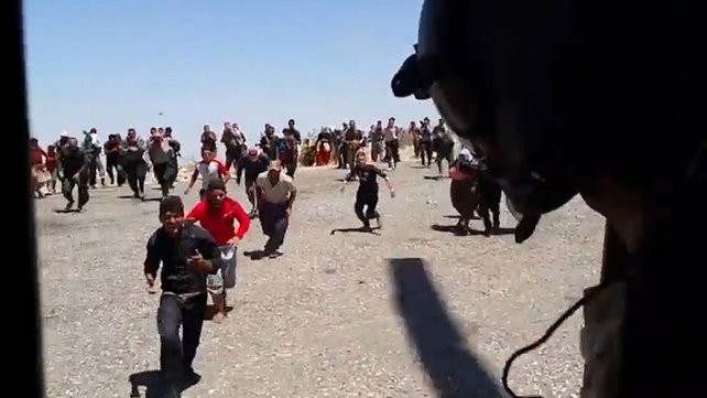 Iraqis stranded on Mount Sinjar run towards a helicopter in an attempt to get off the mountain