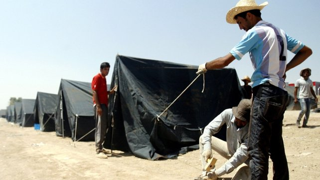 UNHCR staff members erect tents at a new camp in Irbil for Iraqi Christians refugees forced to flee their homes